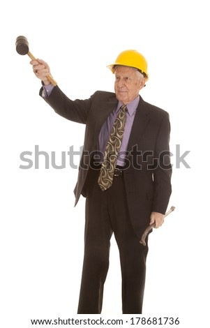 a elderly man in his hard hat holding on to his construction tools. - stock photo