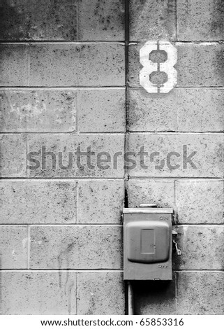 A electrical junction box against a concrete block wall and the number eight. - stock photo