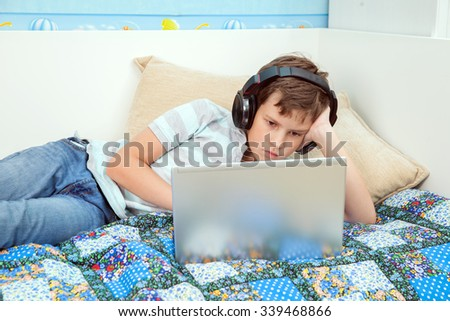 a eleven years boy is working on laptop in his own room - stock photo