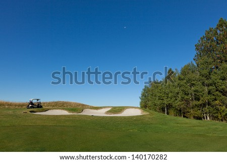 A empty golf cart sitting on a pathway which goes above a sand trap on a golf course with tall trees and a clear blue sky with the moon. - stock photo
