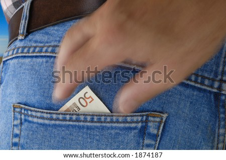 A 50 Euro bill poking out of the rear pocket of a traveller's jeans. Motion blur on a pickpocket's hand, about to take it. - stock photo