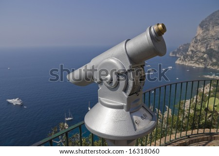 A Euro coin operated set of binoculars looking out over yachts in Capri. - stock photo