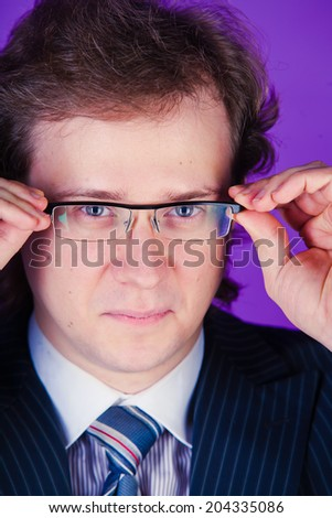 A european caucasian young guy man in a studio on violet purple background with glasses in a suit with a tie  - stock photo