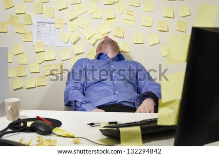 A exhausted / tired business man with his head backwards. Many notes in the background. - stock photo