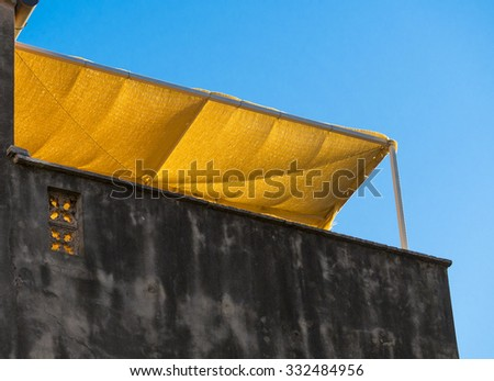 A fabric awning over a roof top patio glows in the late afternoon sun in Venice, Italy. - stock photo