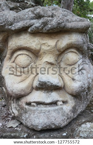 A face carved in stone at the archeological site of the Mayan city of Copan in Honduras Central America - stock photo