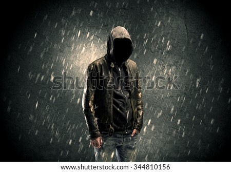 A faceless misterious man in hoodie and leather jacket standing in the dark with a visible silhouette concept - stock photo