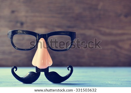 a fake mustache, nose and eyeglasses on a rustic blue wooden surface - stock photo