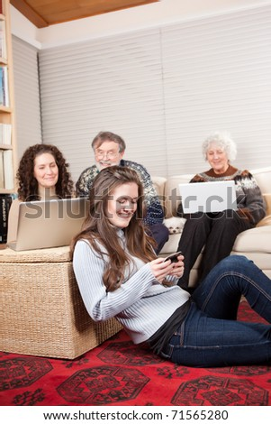 A family at home using wireless technology such as laptop and cell phone