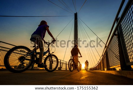 A family bicycles across the Bob Kerry pedestrian bridge over the Missouri River from Council Bluffs Iowa to Omaha Nebraska during the summer. - stock photo