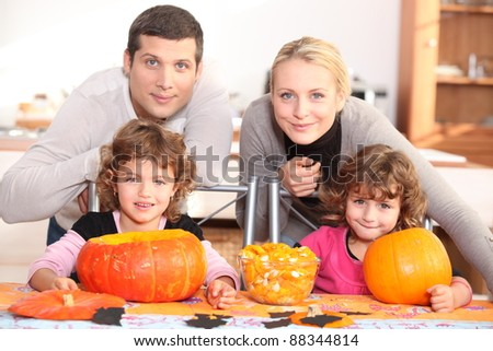 A family carving Halloween pumpkins. - stock photo
