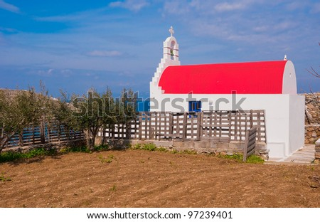 A family church and a garden with olive trees on the background of the sea. Mykonos, Greece. - stock photo