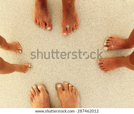 a Family feet on the sand on the beach - stock photo