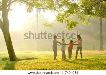 a family having fun playing in the early morning - stock photo