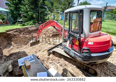 A family house is being rebuilt with the help of an excavator - stock photo