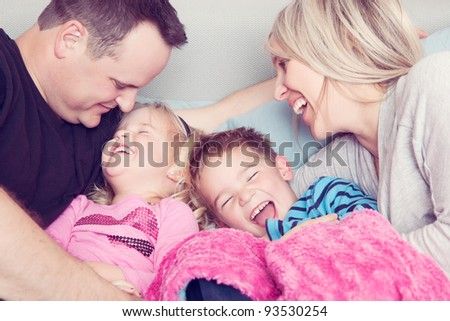 A family in bed laughing together. - stock photo