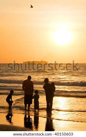 A family of five at the ocean at sunrise with a ship in the background.