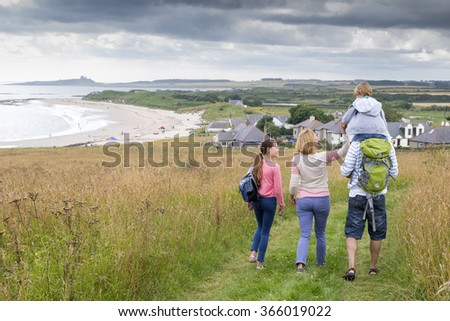 A family of four are walking along the sand dunes. The little boy is getting carried on his fathers shoulders. - stock photo