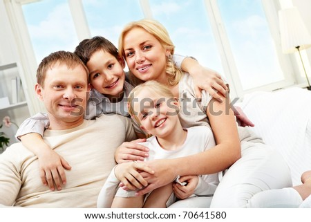 A family of four sitting on sofa, embracing and smiling - stock photo