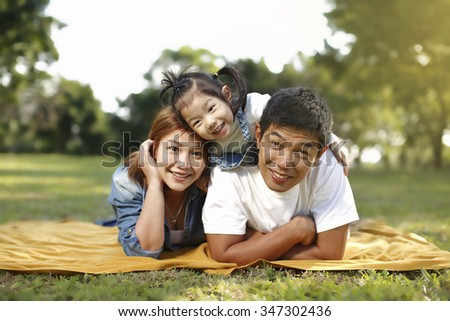 A family of three enjoy a beautiful morning at the park. - stock photo