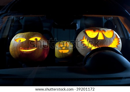 A family of three jack o' lantern pumpkins sitting in a car.
