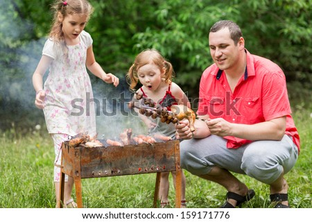 A family of three making barbecue on the grill on nature, little girl blowing on a skewer with mushrooms. - stock photo