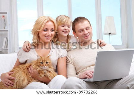 A family of three with cat sitting on sofa and looking at laptop screen
