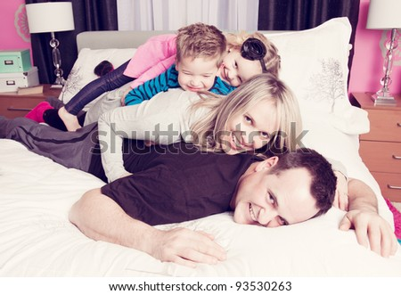 A family piled on top of each other in a bedroom. - stock photo