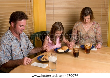 A family saying grace together. - stock photo
