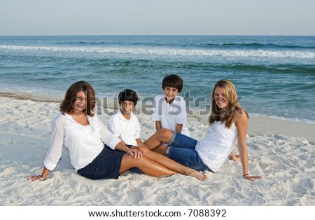 A family sitting together on the beach. - stock photo