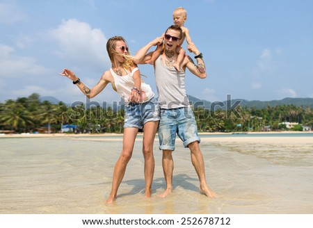 A family spending their leisure time on the beach. The father carring his son on his shoulders. - stock photo