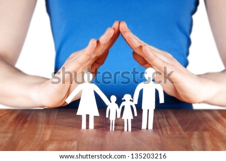 a family standing under a roof of a house build of hands - stock photo