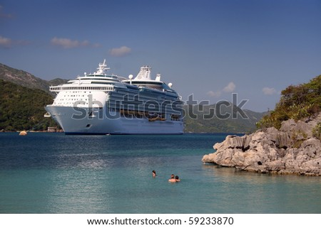 A family swims in a tropical location (Caribbean) in front of large cruise ship. - stock photo