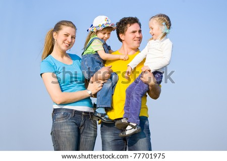 A family with two children at the background of the sky - stock photo