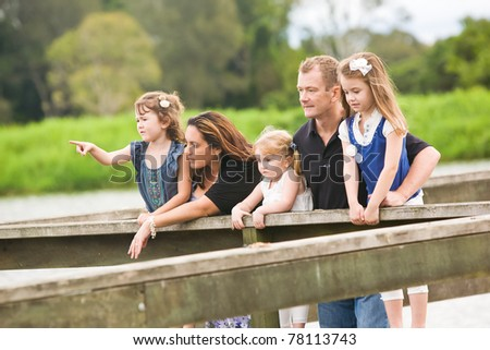 A family with young children together looking outward