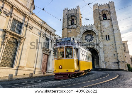 A famous yellow tram 28 passing in front of Santa Maria cathedral in Lisbon, Portugal - stock photo