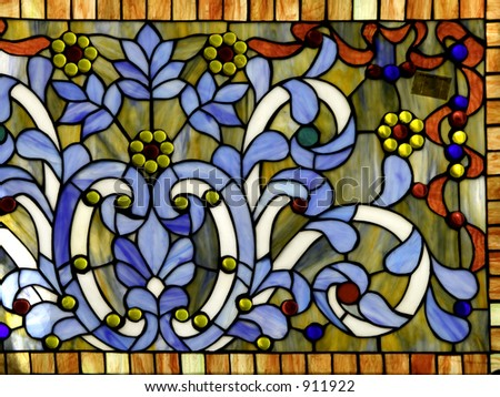 A fancy curved stained glass panel showing brilliant primary colors. - stock photo