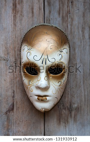 A fancy mask on the wood wall.