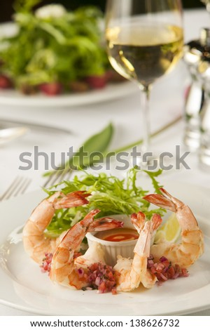 A fancy shrimp cocktail appetizer in a restaurant setting.