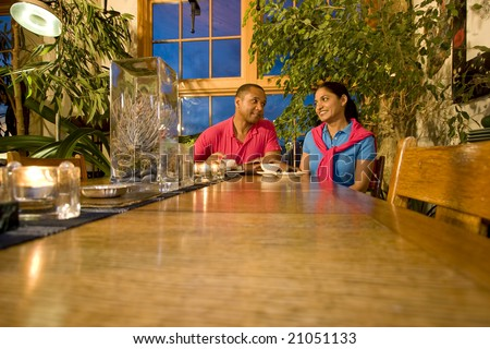 A far away view of a multi-ethnic couple.  They are smiling at one another. They are sitting at a table and have a teapot and teacups.  Horizontally framed shot. - stock photo