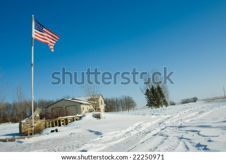 A farm house covered of snow an with an american flag in front of it. - stock photo