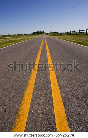 A farm road or highway on a beautiful cloudless day - stock photo