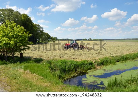 A farm tractor pulling a hay rake in a field to clew the grass in a Dutch landscape - stock photo