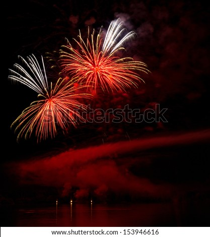 A fascinating fireworks on a lakeside - stock photo