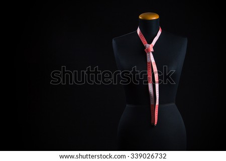 A fashion mannequin with a tailor meter around the neck in the shape of a tie - stock photo
