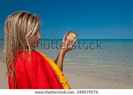A fashion model investigating a sea shell on an isolated beach with clear blue water - stock photo