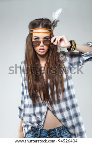 A fashion portrait of a beautiful young brunette dressed in hippie style. She is wearing a sunglasses, plaid shirt, skinny jeans and bandu. Taken in studio against a gray background. - stock photo