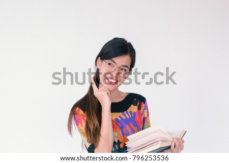 A fashion portrait Young Asian student wearing colourful vintage outfit holding a book