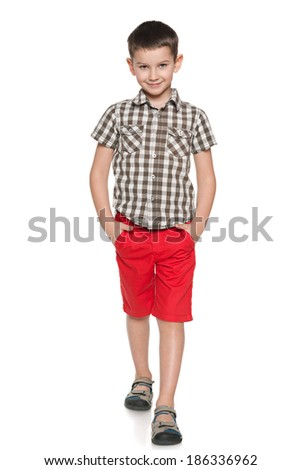 A fashion smiling little boy walks against the white background - stock photo