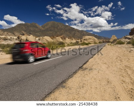 A fast car on the road in a arid and rocky landscape. - stock photo